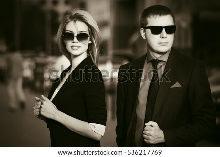 Young business couple walking on city street. Stylish fashion model in sunglasses outdoor