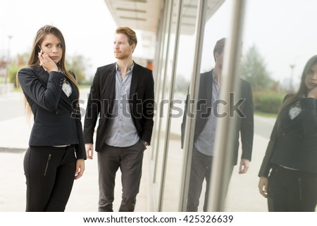 Young business couple walking outside while woman is on the phone