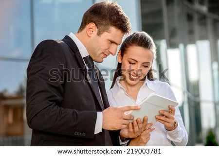 Young Business couple with digital tablet talking and working aganst contemporary building