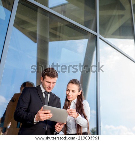 Young Business couple with digital tablet talking and working aganst contemporary building - stock photo
