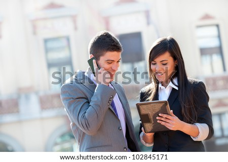 Young Business couple working outdoors with digital tablet.