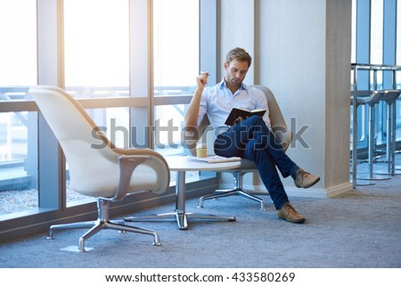 Young business entrepreneur with modern style, sitting in an open corporate space, reading through notes in his diary, alongside large windows - stock photo