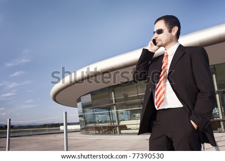 Young business executive in black suit and sunglasses talking on cell phone with office building and blue sky in background.