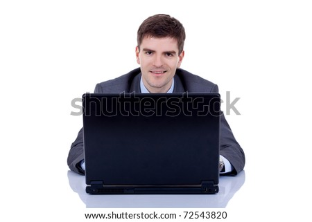 young business executive in suit behind desk with laptop - stock photo