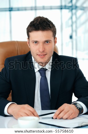 Young business executive sitting in chair attentively looking at you. - stock photo