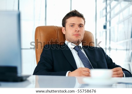 Young business executive sitting relaxed in chair looking at you.
