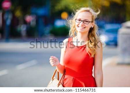 Young business girl in red dress on blurry city background - stock photo