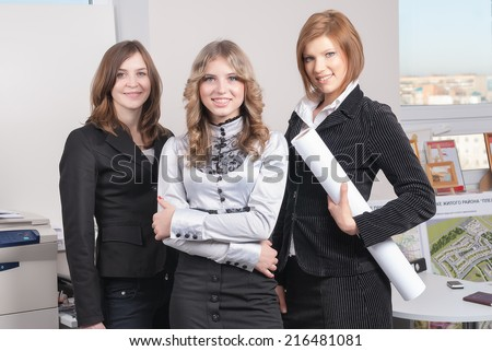 "Young business group of pretty women in architectural office (title on background: ...ke residental district ""Ple...)"
