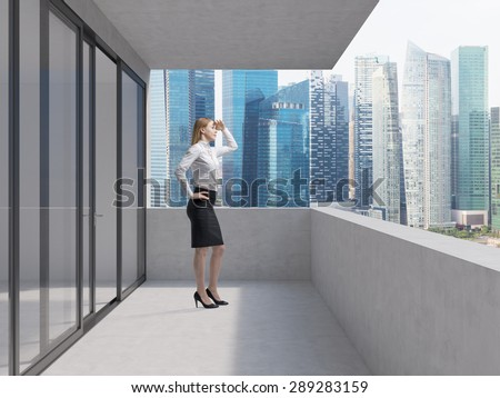 Young business lady is standing on the balcony of the skyscraper and looking at the new business perspectives. Singapore panoramic view.