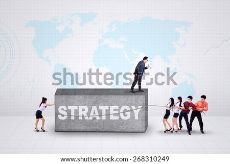 Young business leader and his team use a strategy to remove an obstacle - stock photo