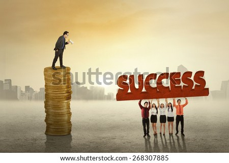Young business leader standing on the stack of golden coins while giving order to his employees - stock photo