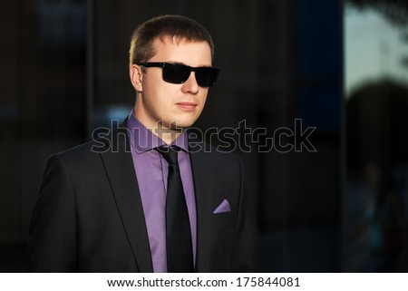 Young business man against office building - stock photo