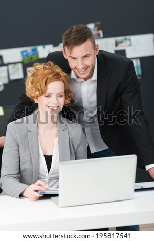 Young business man and woman smiling happily as they read information on the screen of a laptop computer - stock photo