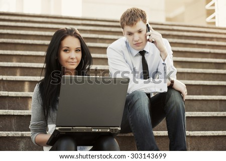 Young business man and woman with laptop on the steps - stock photo