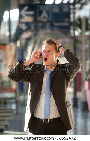 Young business man angry at telephon - stock photo