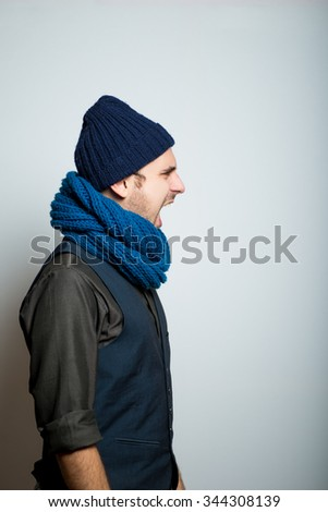 young business man angry shouts winter style clothes, studio shot isolated on the gray background - stock photo
