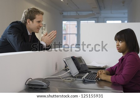 Young business man begging woman in office cubicle - stock photo