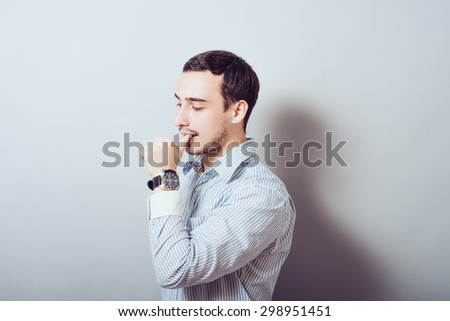 young business man biting his nails while looking into the camera. on a light gray studio background - stock photo