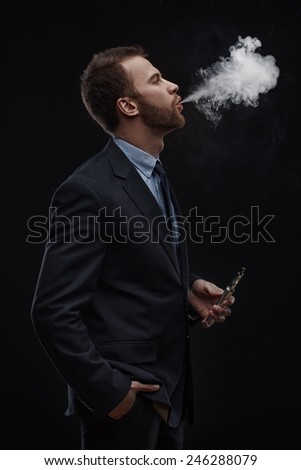 young business man blowing smoke of electronic cigarette on dark background - stock photo