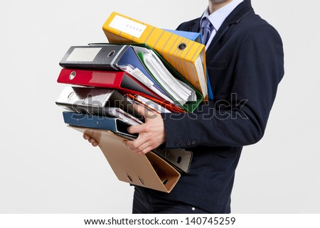 Young business man carrying a bunch of folders - stock photo