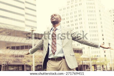 Young business man celebrates freedom success arms raised looking up to sky. Positive human emotions face expression feelings  - stock photo