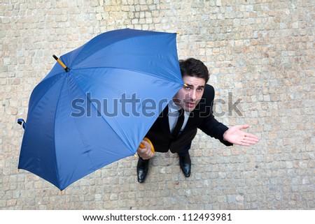 Young business man checking if it's raining - stock photo