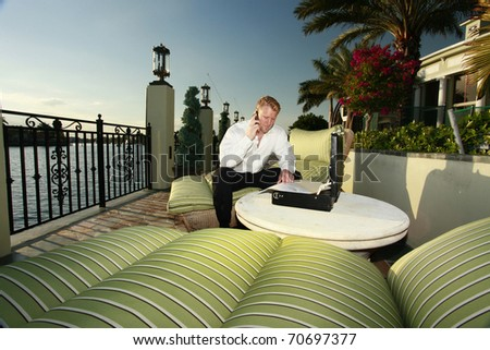 Young business man closing deals on the waterfront - stock photo