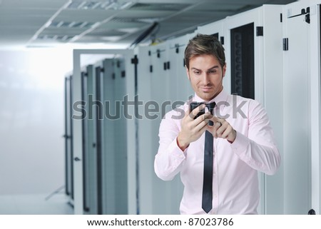 young business man computer science engeneer talking by cellphone at network datacenter server room asking  for help and fast solutions and services - stock photo
