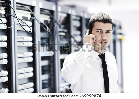 young business man computer science engineer talking by cellphone at network data center server room asking  for help and fast solutions and services - stock photo