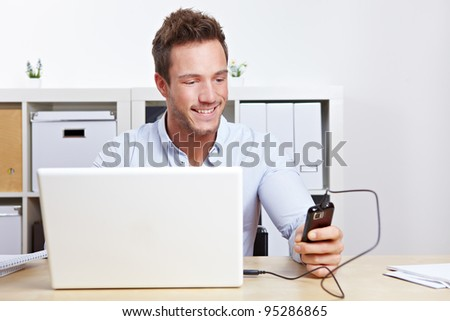 Young business man connection cell phone to computer in office - stock photo