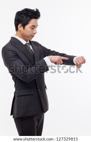 Young business man consulting his watch, isolated over white