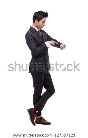 Young business man consulting his watch, isolated over white - stock photo