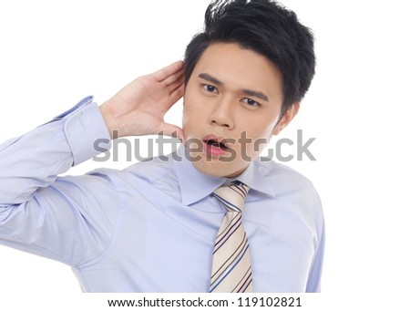 Young business man cupping hand behind ear on white background