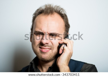 young business man disappointed on the phone, the manager of office concept, shot isolated on gray background - stock photo