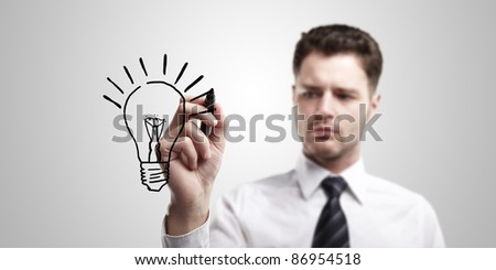 Young business man drawing a light bulb on a glass screen with black marker. Man coming up with an idea. On a gray background - stock photo