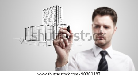 Young business man drawing a project of building on a glass window. Portrait of young architect thinking about construction. On a gray background. - stock photo