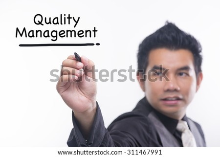 Young business man draws a word quality management - stock photo