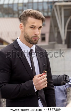 Young business man eating chocolate outdoors