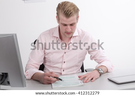 young business man filling out forms at desk