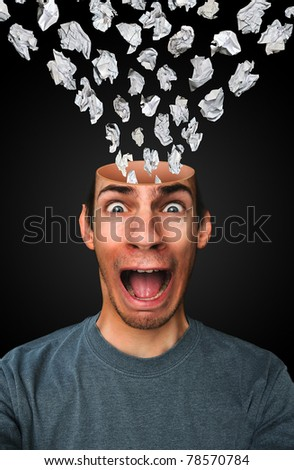 Young business man getting stressed and overwhelmed by large amounts of paper work and school work. - stock photo