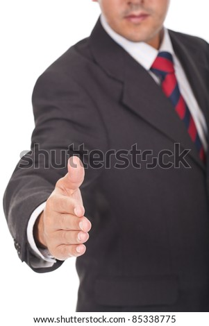 young  business man giving you a hand shake - stock photo