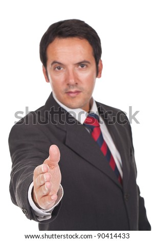 young  business man giving you a hand shake (focus is on the hand) - stock photo