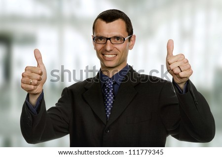 young business man going thumbs up at the office - stock photo