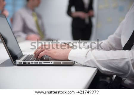 young business man hands typing on laptop  computer  on meeting, blured people group brainstorming in background  at modern bright office interior