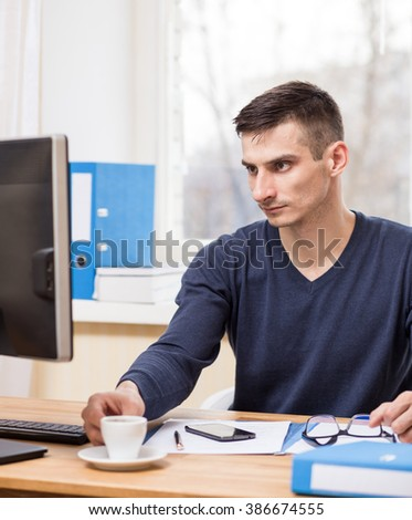 Young business man has morning coffee at his workplace