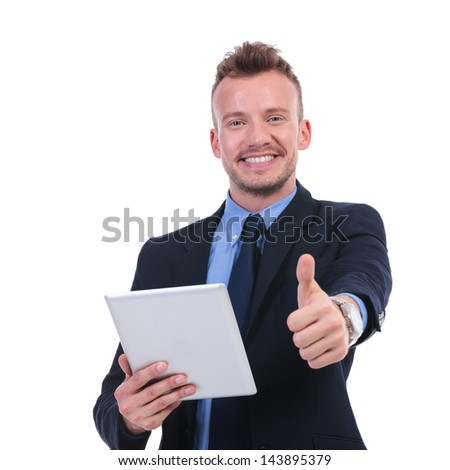 young business man holding a tablet and showing thumb up while smiling to the camera. on white background