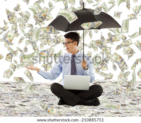 young business man holding a umbrella with dollar rain - stock photo