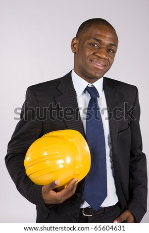 Young business man holding a yellow helmet - stock photo