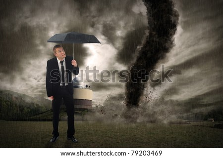 Young business man holding an umbrella in front of a tornado