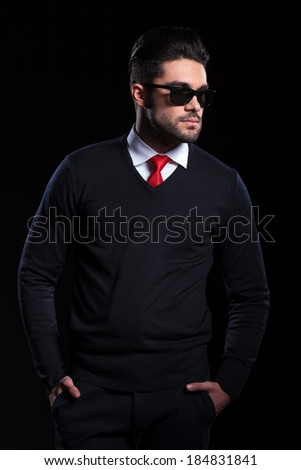 young business man holding both hands in his pockets and looking away with a serious expression. on a black background